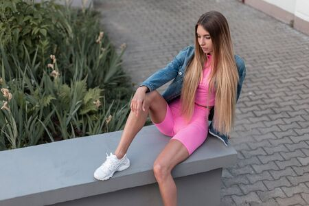Slim glamorous young woman blonde in a fashionable blue denim jacket in stylish pink shorts in trendy white shoes sits on the street. Pretty beautiful girl enjoys a summer day. Modern street fashion.