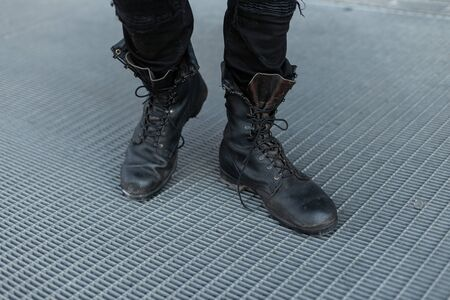 Male legs closeup. Stylish young man in trendy jeans in vintage black leather boots. Details of everyday look. Old-fashioned style. Close-up.