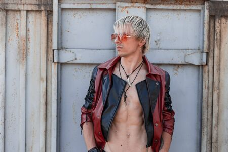 Sexy young man blond with a naked torso in a fashionable leather jacket in trendy red sunglasses is posing near a vintage gray building. Foto de archivo - 126648291