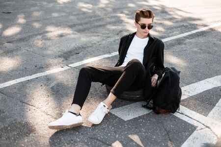 Modern young man hipster in elegant black clothes in white trendy sneakers with a backpack in sunglasses sits on a rubber wheel on the street. Urban guy relaxes in the sun outdoors on a summer day.