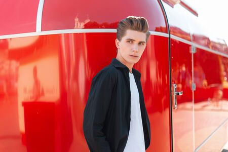 Elegant handsome young man with stylish hairstyle in a black shirt in a white t-shirt rest on the background of a vintage red trailer in the city on a bright sunny day. European guy fashion model.