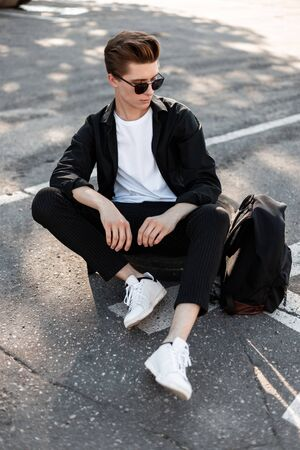 Attractive young man in an elegant shirt in stylish sunglasses in pants with a backpack in trendy sneakers sits on the asphalt on the street. Handsome hipster guy relaxes in the city on a sunny day. Foto de archivo - 127601902