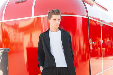Modern elegant young man with a stylish hairstyle in a fashionable black shirt in a white T-shirt in trousers poses near a red vintage trailer in the city. Urban european guy fashion model. Style. Foto de archivo - 127601905