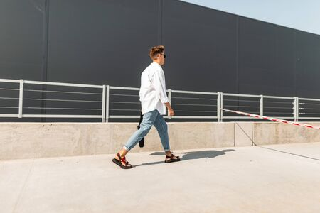 Young man with a trendy hairstyle in a white shirt in vintage blue jeans in leather sandals with a black bag walks down the street near a gray building. Modern stylish guy on a walk on a sunny day. Foto de archivo - 127601910