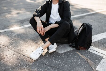 Close-up of male fashionable legs . Young fashion man in elegant black shirt in striped vintage trousers in white sneakers with stylish black backpack sits on asphalt.. collection of trendy menswear.