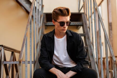 American young man hipster in an elegant shirt in a t-shirt in trendy sunglasses sits on an iron staircase in the city. Handsome guy with a stylish hairstyle resting on the street.Fashionable menswear