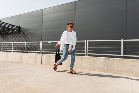 New collection of stylish summer menswear. Handsome young hipster man in fashionable clothes in vintage sunglasses with a hairstyle with a bag in sandals poses in the city on a sunny summer day.