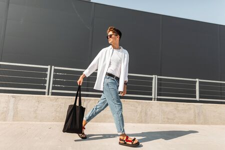 American trendy young man in stylish clothes in red sandals with a fabric bag in sunglasses is traveling on the street near the gray building. Stylish guy outdoors. New collection of summer clothes. Foto de archivo - 127602079