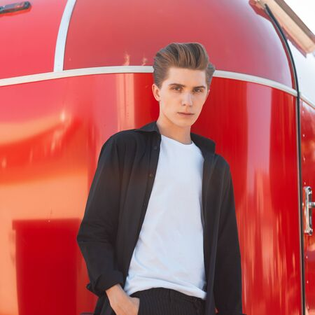 European serious young man in a stylish shirt in a white T-shirt with a trendy hairstyle poses near a vintage red trailer in the city. Handsome guy enjoys rest bright summer sunny day in the street. Foto de archivo - 127602411