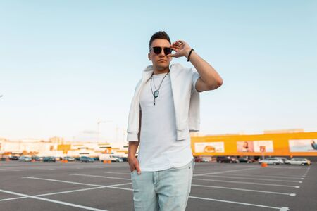 Stylish guy hipster straightens dark sunglasses. Handsome young man in trendy summer clothes is standing in a parking lot on a clear summer day. Trendy new collection of men's clothing and accessories 免版税图像