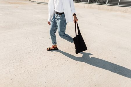 Closeup of male legs in stylish jeans in red leather summer shoes with a cloth black vintage bag. Young urban man goes on the pavement. New trendy collection of men's shoes. Street style.