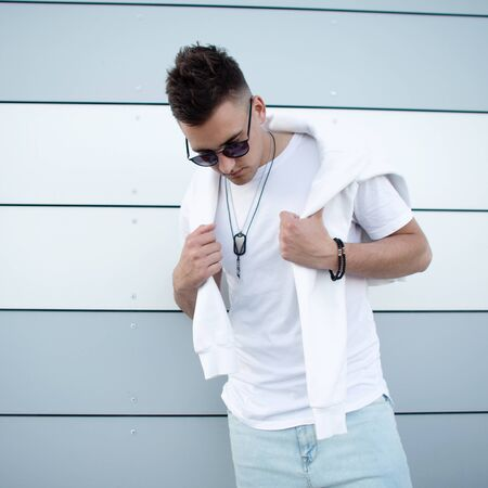 Handsome nice young hipster man in trendy white t-shirt in stylish sunglasses with fashionable hairstyle posing near a modern building in the city. Urban guy fashion model outdoors. Summer style. Foto de archivo - 129094450