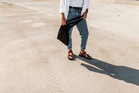 Trendy men's legs in blue vintage jeans in stylish red leather sandals with a black fabric bag stand on the pavement. Fashionable new summer collection of menswear and shoe. Close-up