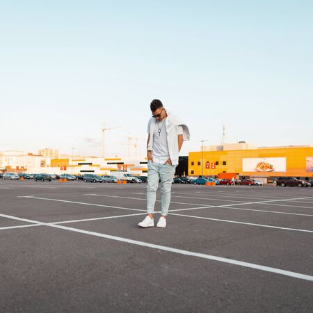 American young hipster man in sunglasses in blue jeans in white sneakers in a trendy T-shirt with a sweatshirt travels down the street. Handsome urban guy in the parking lot. Stylish summer menswear. 免版税图像