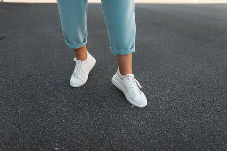 Female legs in stylish blue pants in white leather sneakers on the asphalt in the city. Trendy young woman on a walk. Fashionable womens shoes. New collection.