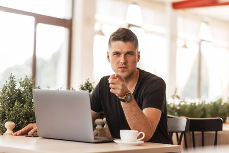Attractive young businessman in a stylish black t-shirt points a finger at the camera. Successful guy freelancer works on a laptop on the Internet sitting in a cafe. Remote work.