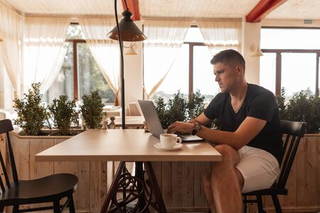 Stylish young man freelancer in fashionable clothes sits at a table in an vintage cafe and works on a modern laptop at lunch time. Business guy. Remote work. Imagens