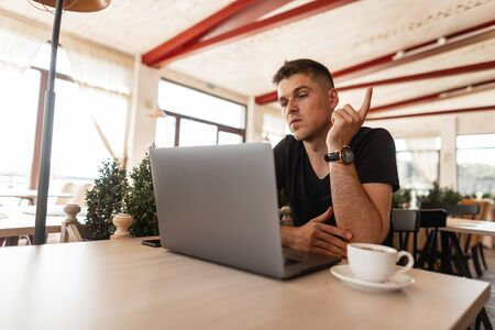 Young attractive business man in a stylish black t-shirt sitting in a cafe and working remotely on a modern laptop. Handsome freelancer guy. Work time.