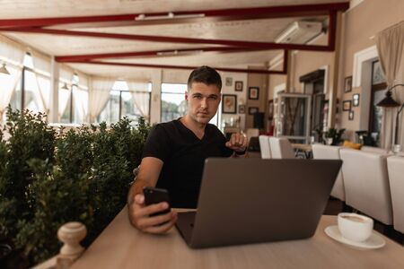 Successful young man blogger in stylish clothes is broadcasting live online from the phone while sitting in a vintage cafe. Modern business guy freelancer looks in the smartphone. Remote work.