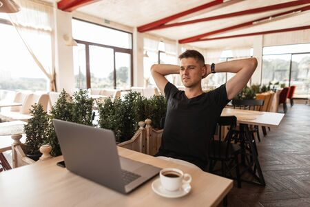 Successful joyful young business man in a black t-shirt with a computer sits in a modern cafe. Happy freelancer guy working remotely on a laptop.  Relax time.