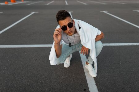 Modern young hipster man in blue jeans in white sneakers in a trendy T-shirt with a sweatshirt sitting on a asphalt and look in the camera. Cool urban guy relaxes in the parking lot. Stylish menswear.