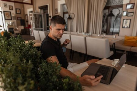 Successful handsome young freelancer in a fashionable T-shirt sits at a wooden table in a vintage cafe with a notebook and looks into the phone. Attractive blogger is broadcasting live online.