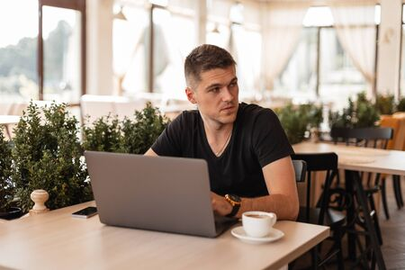 Young handsome business man in a stylish black t-shirt sitting in a cafe and working remotely on a modern laptop. Attractive freelancer guy working remotely.