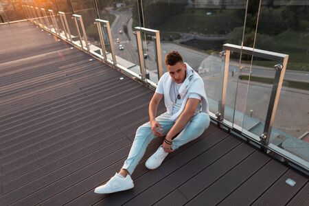 Handsome young man with a hairstyle in a T-shirt in jeans in white sneakers is resting sitting on the floor near a glass wall at sunset.Trendy guy is resting on a summer terrace. View from above.