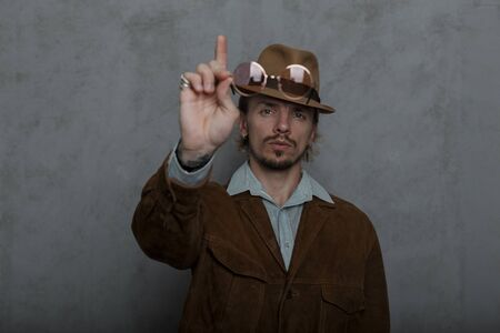Old-fashioned strong young man in a vintage hat in a round glasses in a stylish brown jacket stands near a gray wall in the studio. Brutal hipster guy draws attention raises his index finger up.