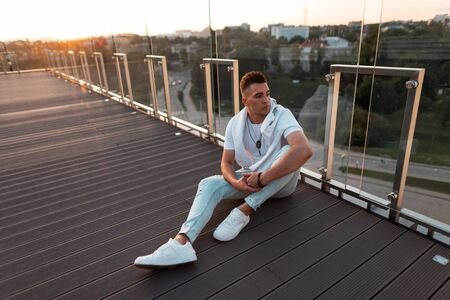 Fashionable handsome young man in stylish clothes in sneakers resting on the floor near a glass wall at sunset in the city. American guy relaxes outdoors on a summer terrace. Stylish mens clothing.