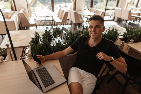 Happy young man in a fashionable black t-shirt is resting while sitting at a table in a vintage cafe with a modern laptop and with a phone in hands. Successful joyful freelancer guy relaxes indoors. Imagens