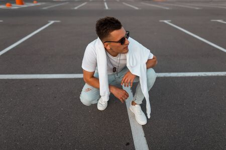 American young hipster man in sunglasses in blue jeans in white sneakers in a trendy T-shirt with a sweatshirt resting on a road. Handsome urban guy posing in the parking lot. Stylish summer menswear.