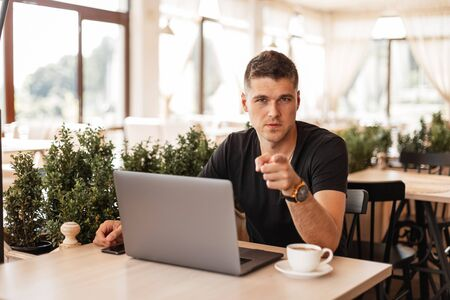 Handsome young business man is sitting in a cafe with a laptop with coffee and is pointing his finger at you. Successful freelancer guy working remotely indoors. Imagens