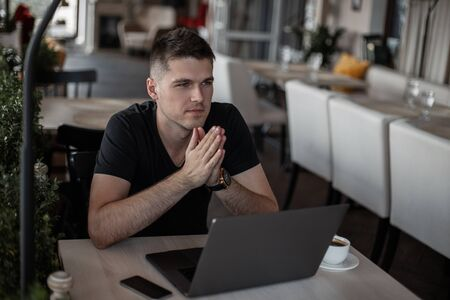 Professional young businessman working on a laptop on the Internet with a new financial project. Freelance guy works remotely in the cafe. Imagens