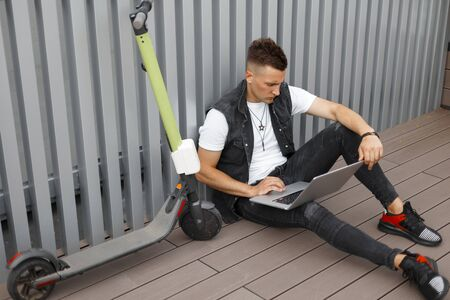 Handsome young man hipster in fashionable denim clothes relaxes on the floor next to an modern electric scooter outdoors in the city. American guy works on a laptop near gray wall.