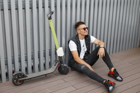 Happy young hipster man with a cute smile in a denim vest in jeans in sneakers in sunglasses sits on the floor next to a modern scooter. Positive guy enjoys is resting after riding an electric scooter Reklamní fotografie