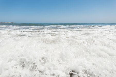 Restless sea with waves with white foam with a clear sunny blue sky. Seascape. Nature composition. Фото со стока