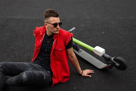 Handsome young hipster man with a hairstyle in stylish denim red-black clothes in sunglasses sitting on a basketball court next to a modern electric scooter. American cool guy is relaxes outdoors.
