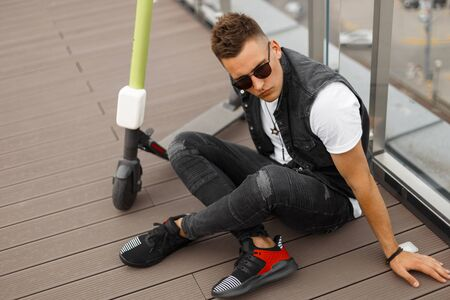 Attractive young hipster man in a gray denim vest in a T-shirt in trendy jeans in sunglasses sitting next to an electric scooter on the outdoor terrace of a summer cafe. Handsome guy is resting.