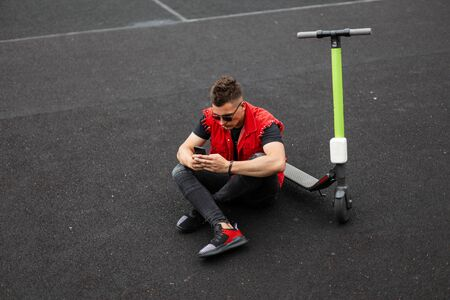 American young man hipster in a red vest in black jeans in sneakers in sunglasses sitting on the asphalt next to an electric scooter and looking at the phone. Attractive modern guy is enjoys vacation.