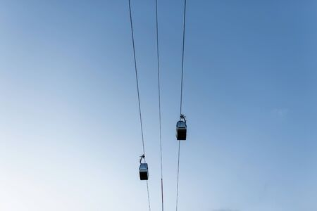 Two electric cable cars on a background of blue clear sky. Resort. Active extreme rest. View from below.