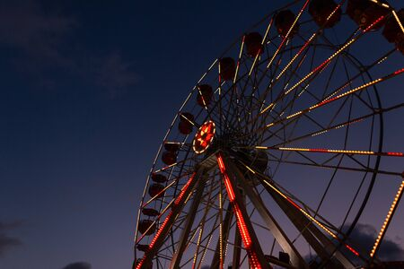 Bottom view on ferris wheels with beautiful bright lamps on a background a dark blue sky. Vintage ferris wheel in the evening.