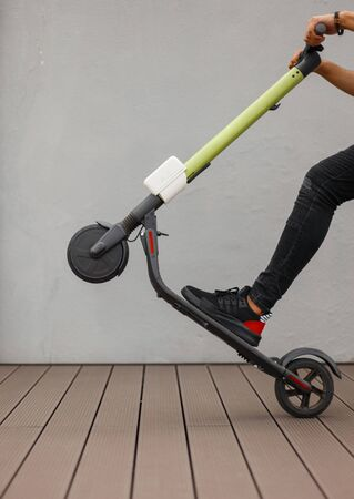 Closeup of a male foot and a modern electric scooter. Guy holds the wheel and raises the scooter on the background of a gray wall. Leisure.