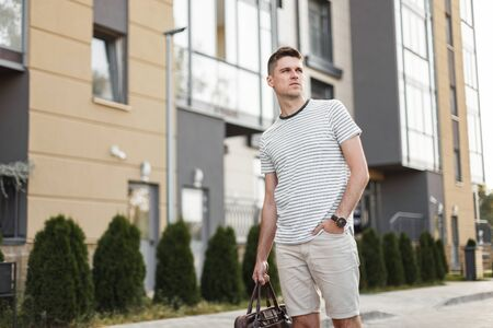 Business young man in a fashionable summer T-shirt in shorts with a trendy leather bag is standing near a modern building. A successful guy walks around the city. New stylish collection of menswear. Imagens
