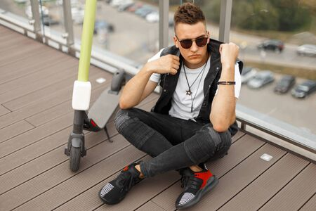 Young modern hipster man in sunglasses in a denim vest in stylish gray jeans in sneakers sitting on a wooden floor next to an electric scooter near a glass wall. Guy is enjoys the weekend in the city.