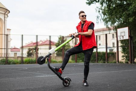 Cheerful trendy young man holds a modern scooter behind the wheel and raises up. Positive stylish hipster guy with smile riding an electric scooter around the city. Active weekend. Healthy lifestyle.