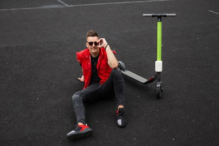 Cheerful young hipster man with a smile in stylish denim red-black clothes straightens sunglasses sitting on a basketball court next to a modern electric scooter. Joyful cute guy is relaxing outdoors.