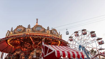 View of the amusement park with a colorful vintage carousel with bright lights and a ferris wheel. Great joyful weekend. Relaxation.