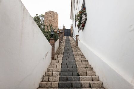 Ancient stone staircase on the historic street of Malaga. Beautiful old white city in spain. View from below. Stock Photo