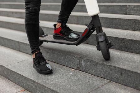 Männerbeine in schwarzen Jeans in Turnschuhen stehen auf einem Elektroroller. Der modische Typ ruht sich aus, nachdem er an einem Sommertag einen Roller gefahren hat, der auf einer Vintage-Steintreppe in der Stadt steht. Standard-Bild
